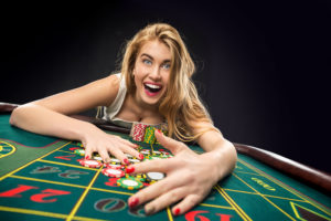 Young blonde hair woman winning big time at casino roulette